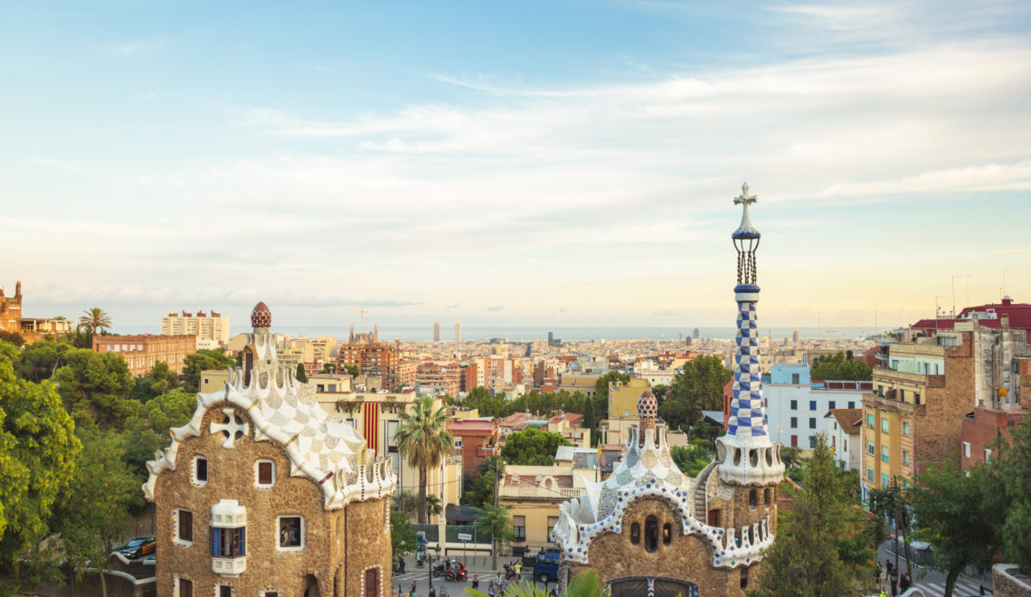 Main entrance to Gaudi's Parc Guell and skyline of Barcelona.